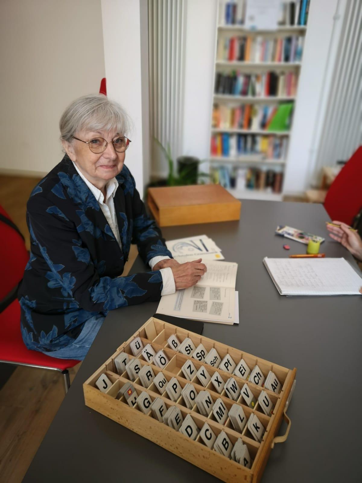 Frau mit grauen Haaren, Brille und blauem Blazer sitzt an einem Tisch, auf dem ein Kasten mit Buchstabenplatten steht