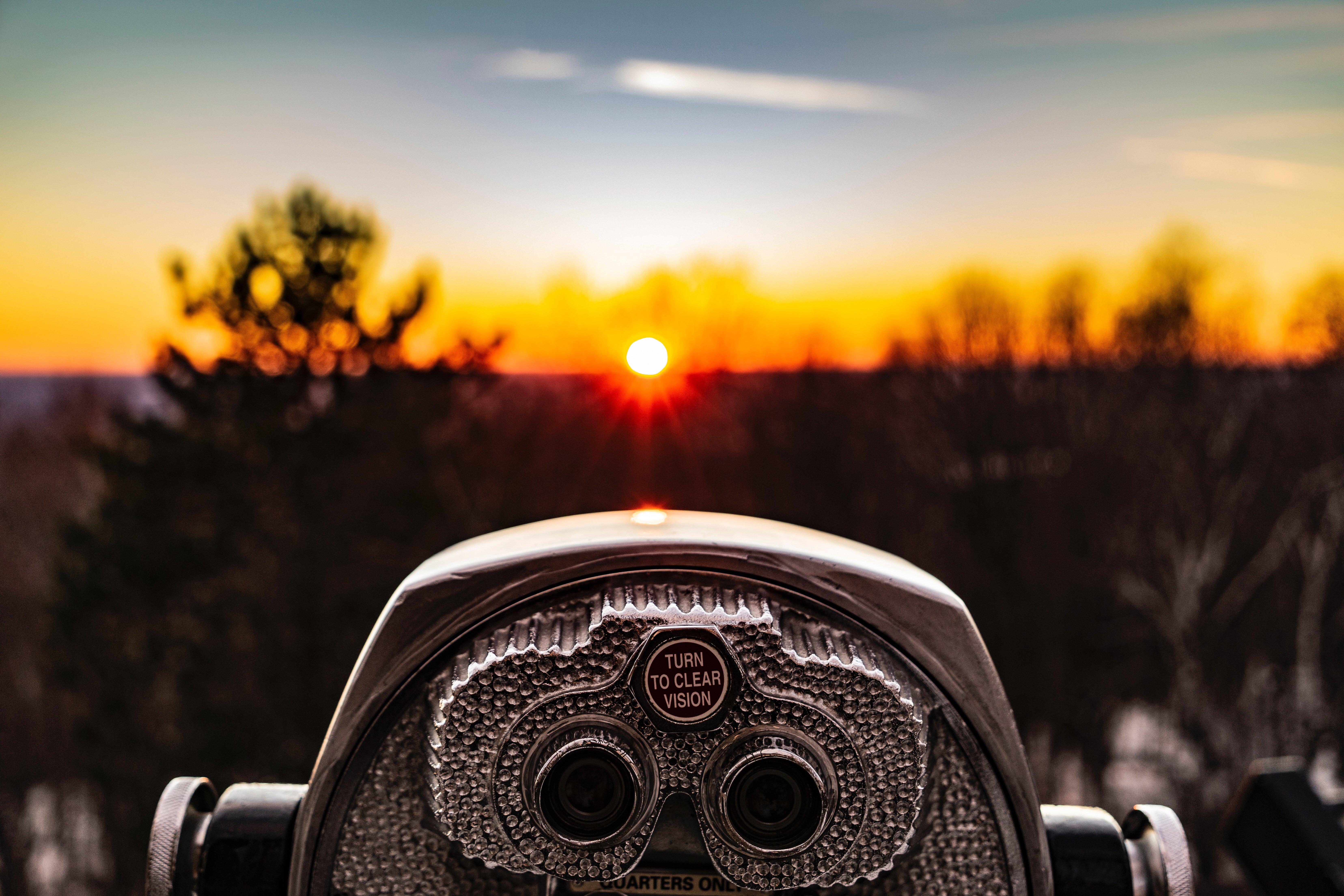 Fernglas im Vordergrund, welches in Richtung der untergehenden Sonne zeigt.