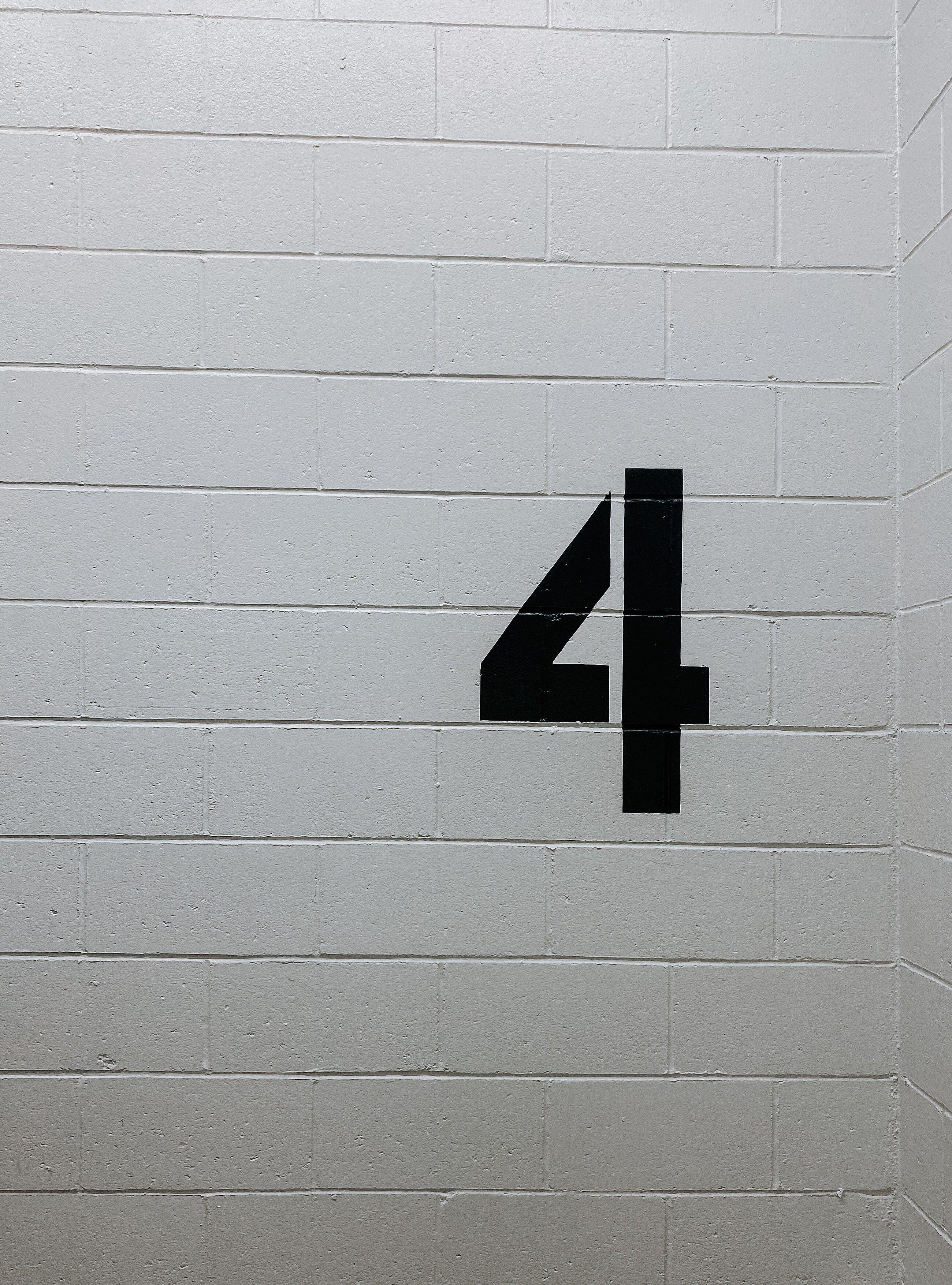 Eine schwarze Vier, die auf eine graue Wand gemalt wurde.