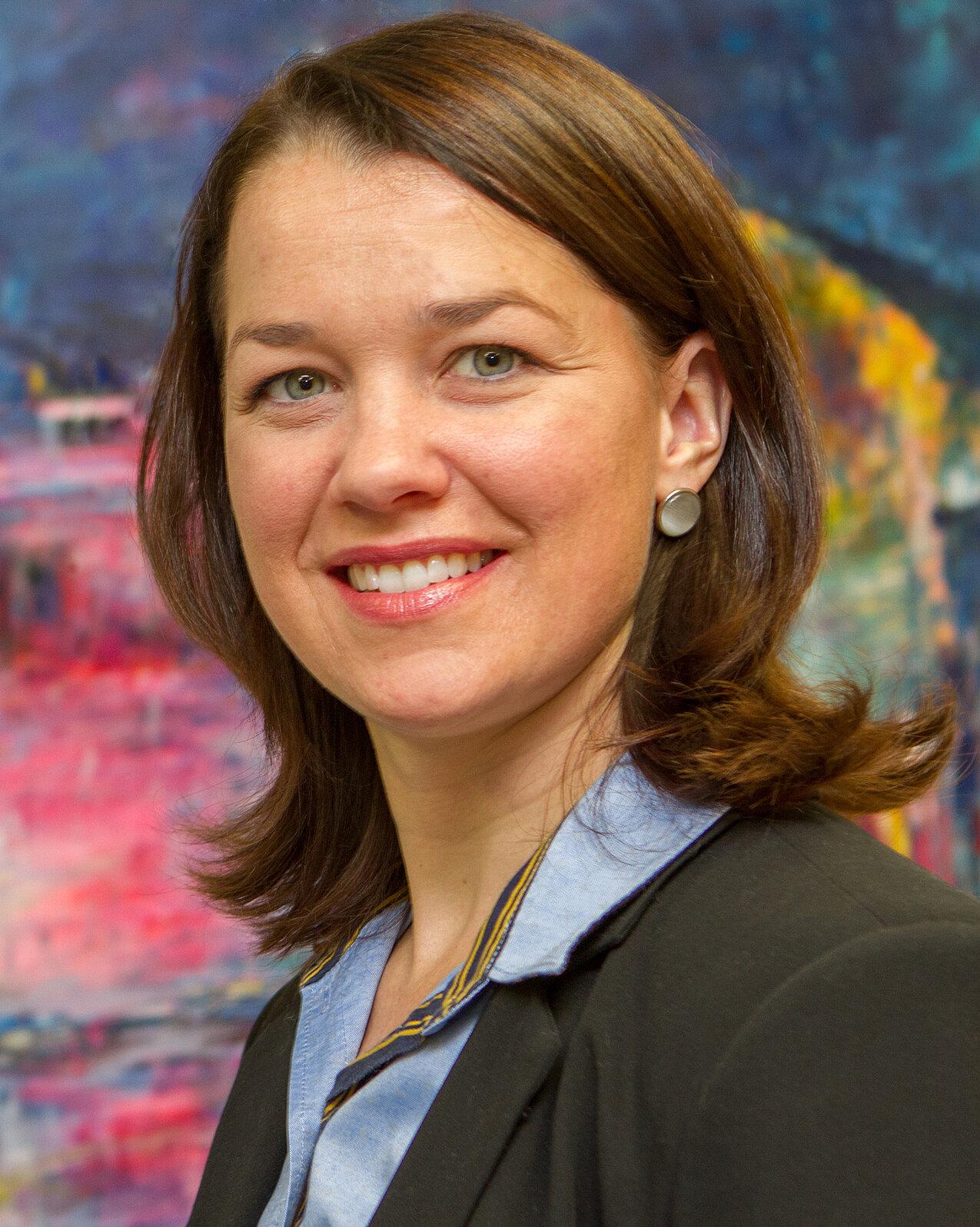 Porträtfoto von Eveline Breyer, sie trägt ein blaues Hemd und hat braune, mittellange Haare.