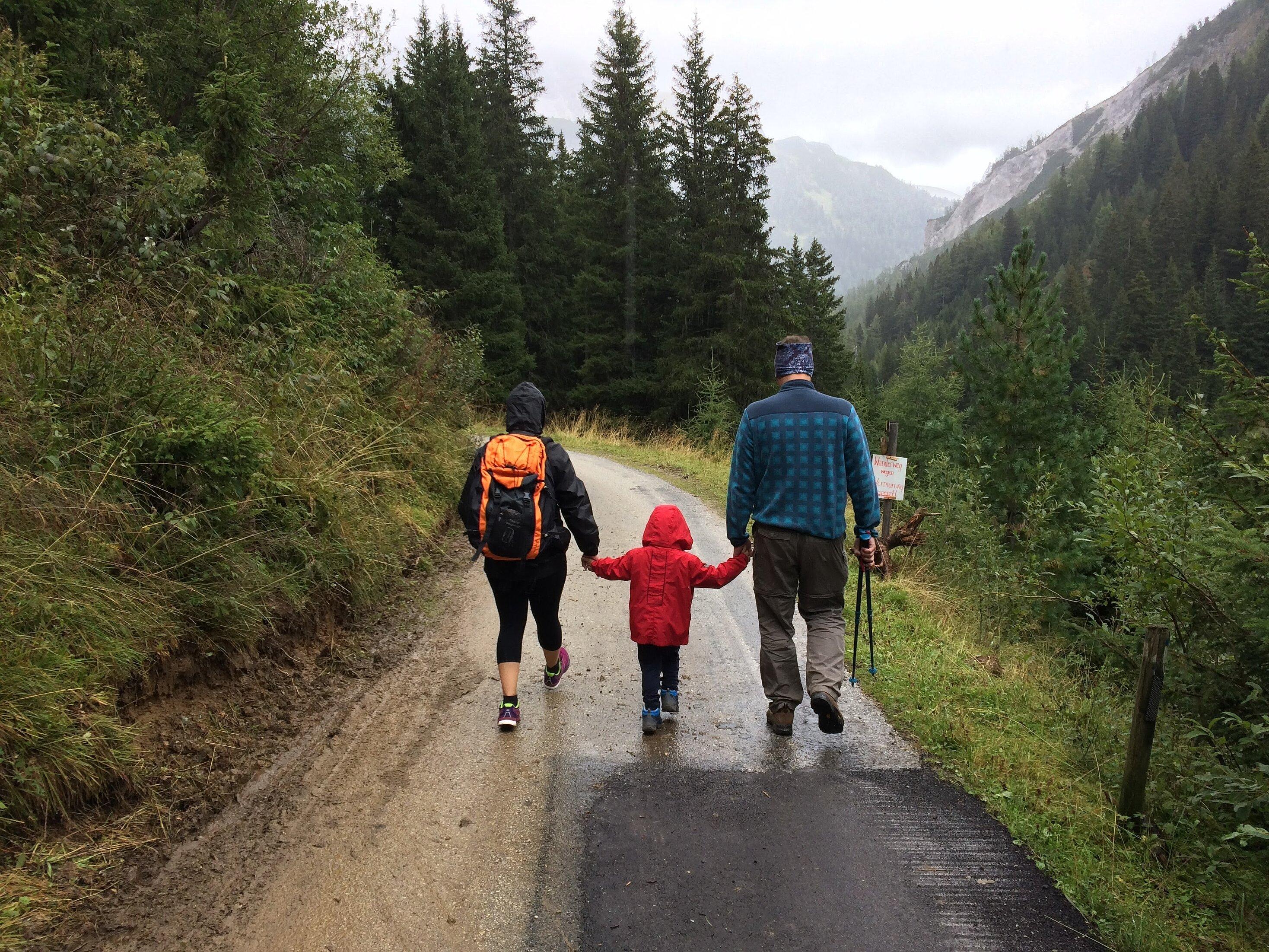 Mutter und Vater, die ein Kind in ihrer Mitte haben und wandern.