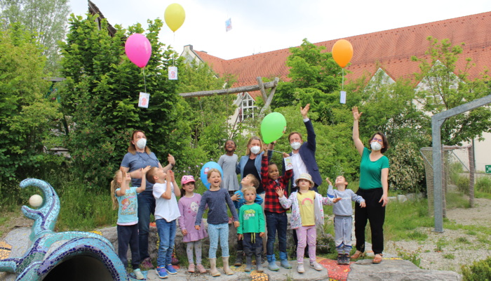 Kinder und Erwachsene lassen bunte, gasbefüllte Ballone mit Karten in die Luft steigen.