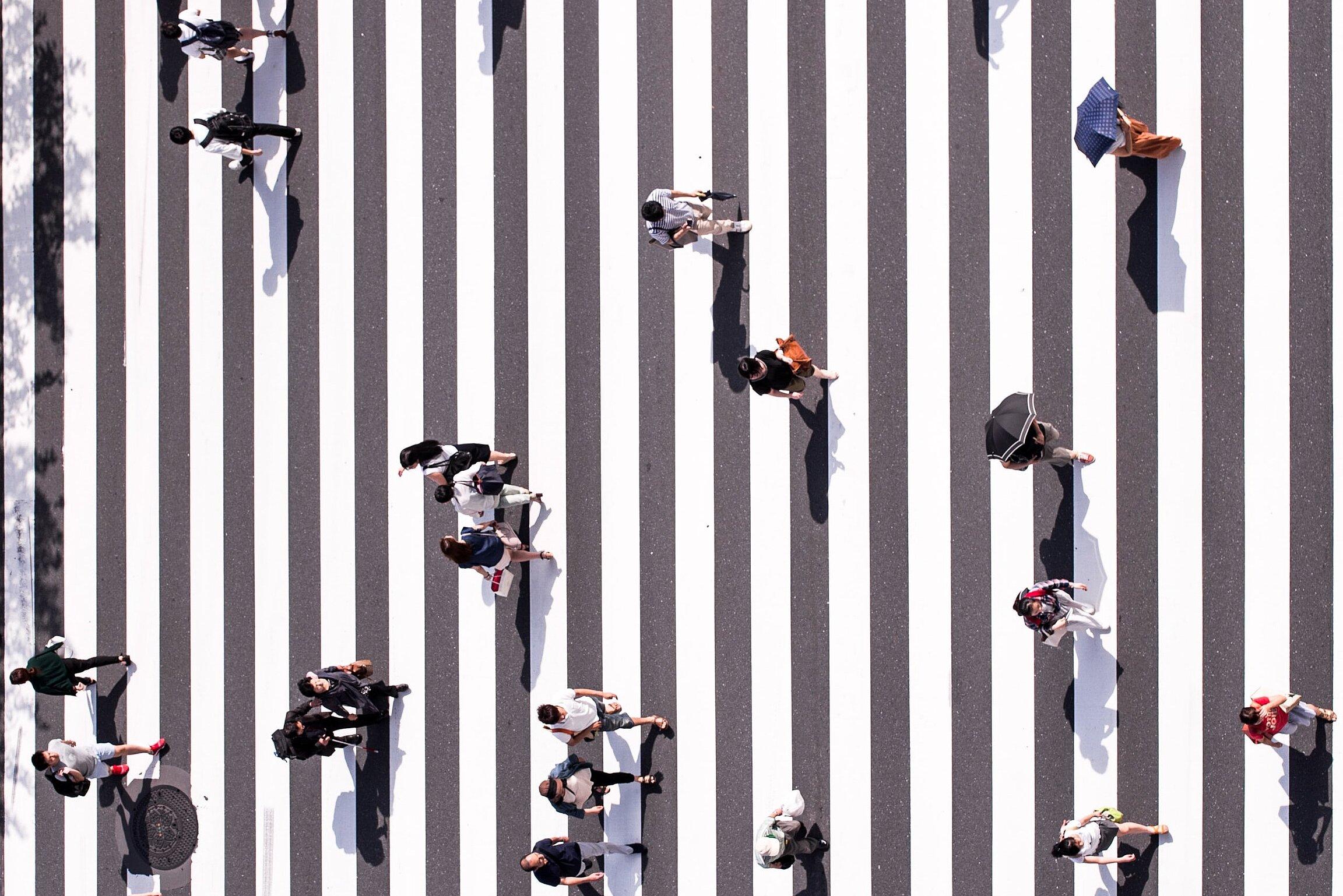 Menschen auf einem Zebrastreifen aus der Vogelperspektive fotografiert.