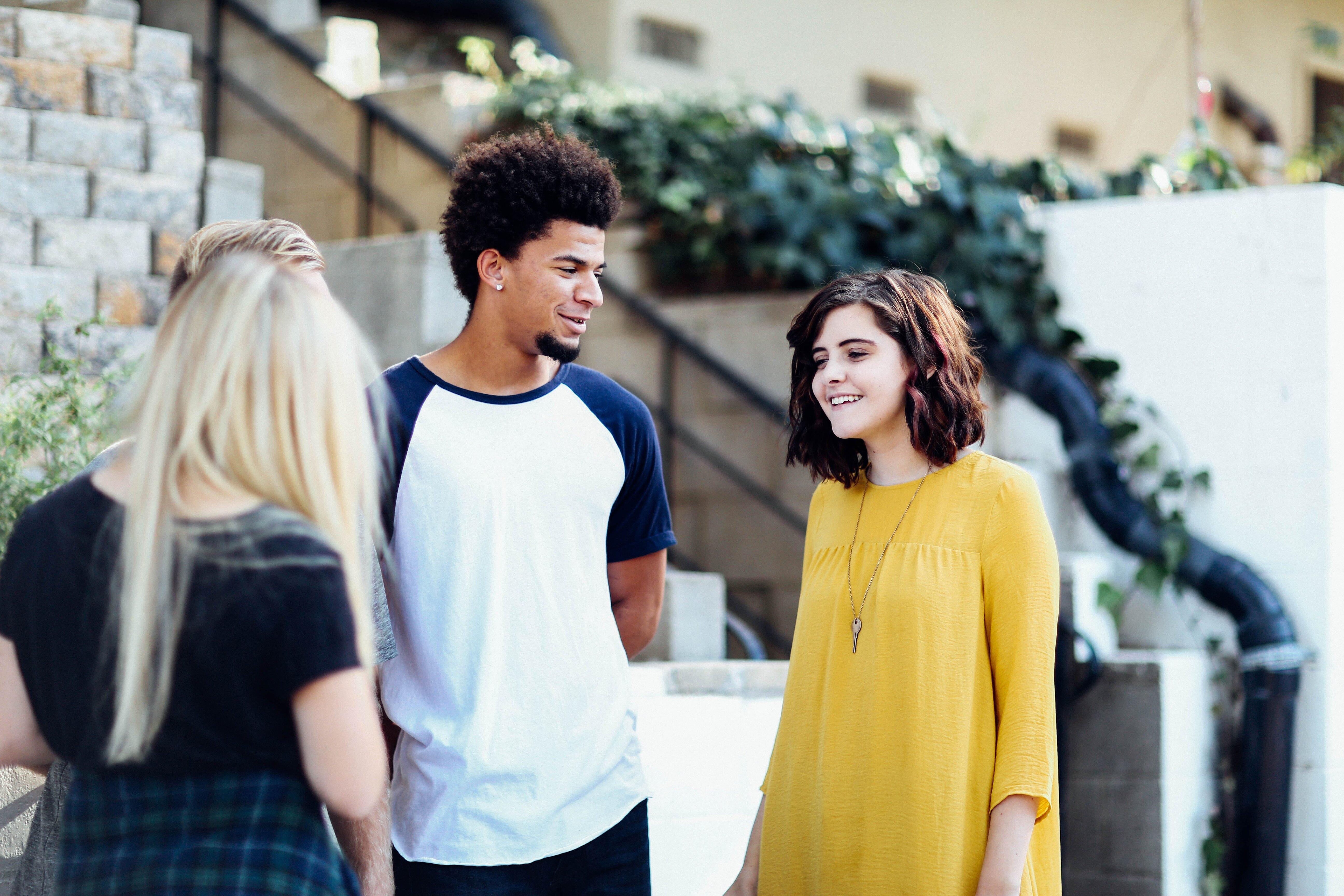 Drei junge Menschen unterhalten sich vor einem Haus