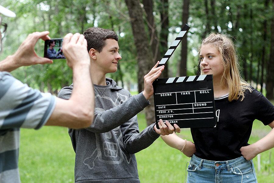 Zwei Jugendliche werden von einem Smartphone gefilmt, einer von ihnen hält eine Filmklappe in der Hand.