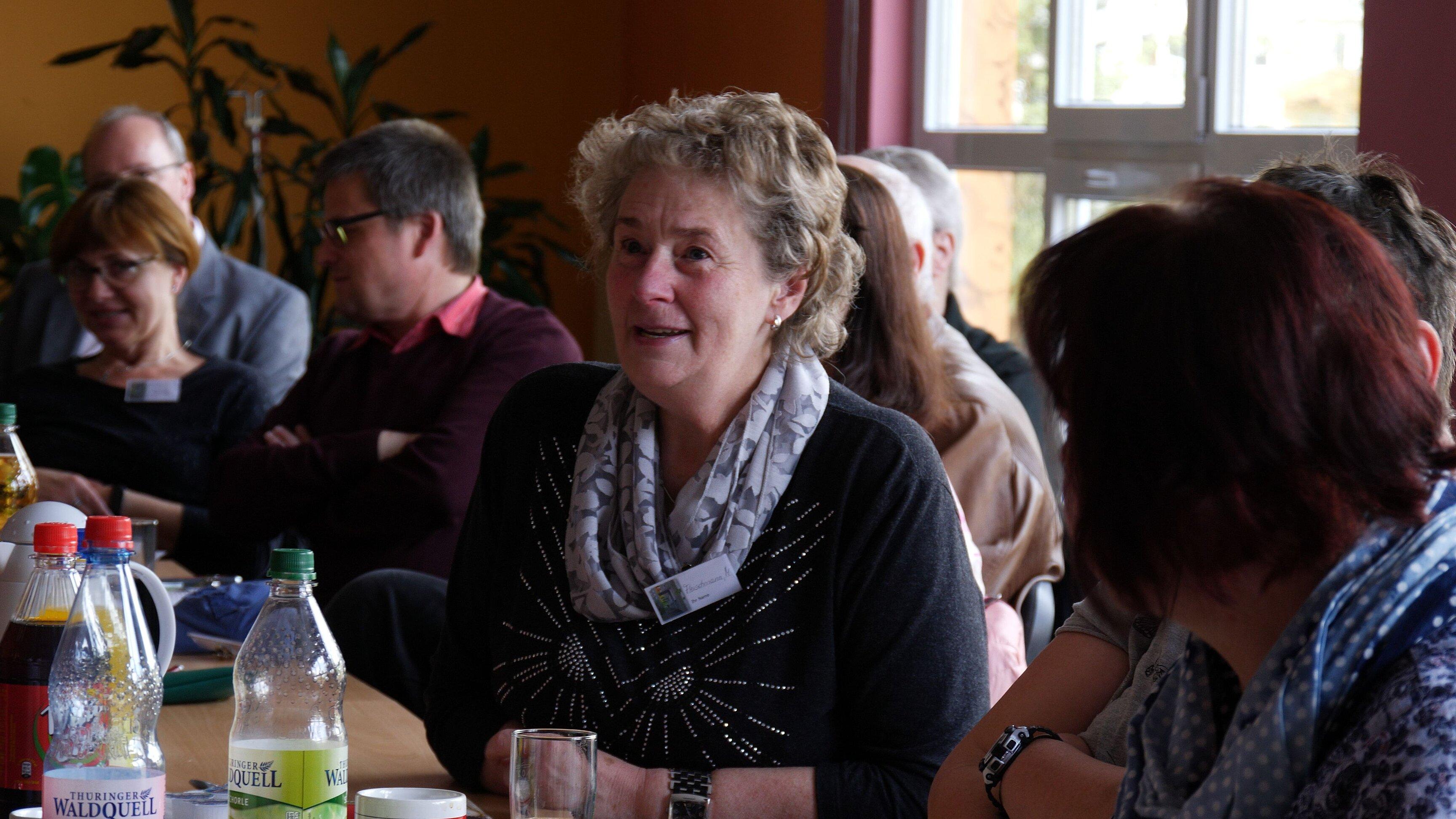 Im Mittelpunkt des Bild sitzt eine mittelalte Frau an einem Tisch, sie ist umgeben von mehreren anderen Personen.