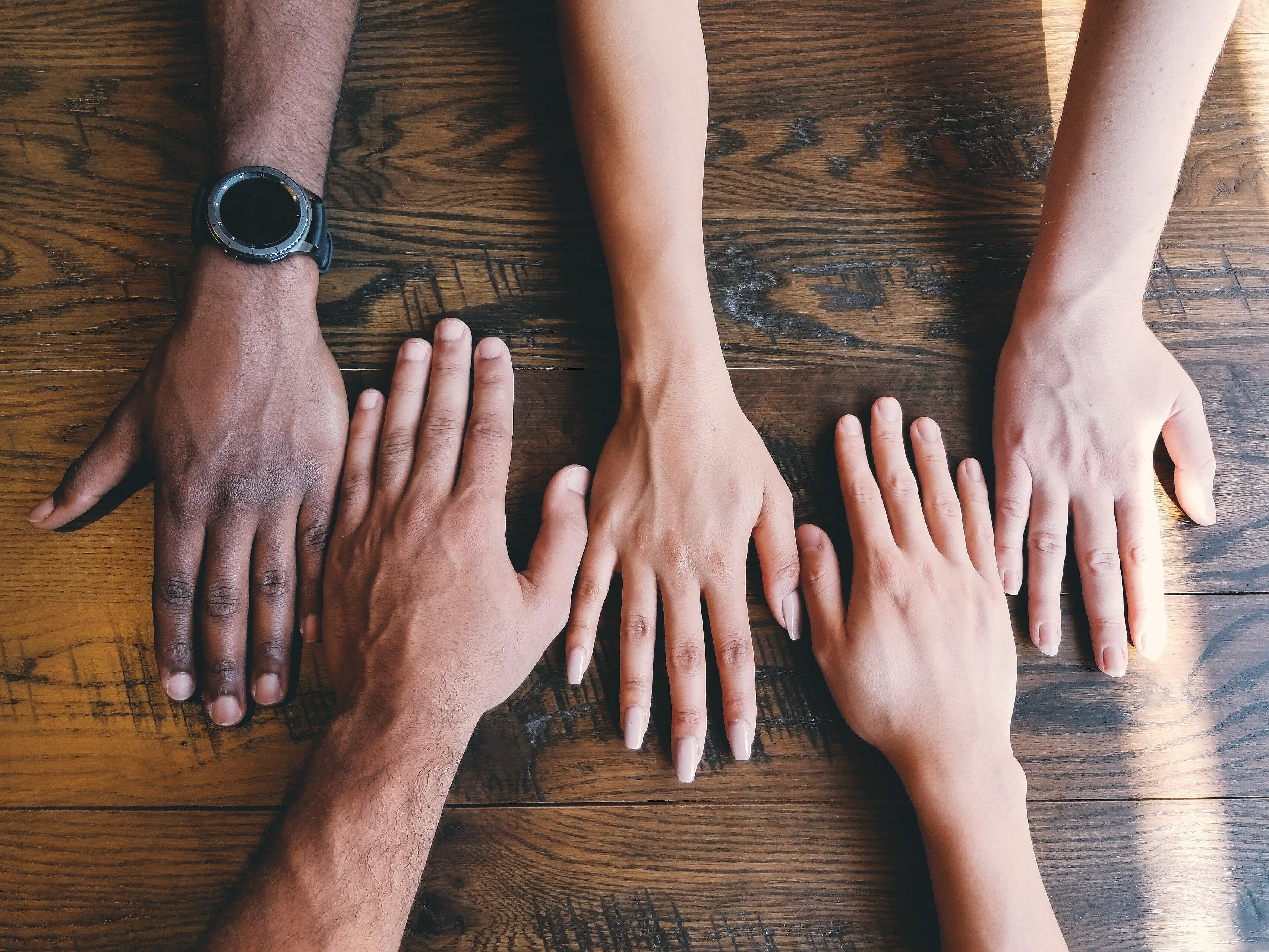 Arme und Hände von verschiedenen Personen, die auf einem Tisch liegen.