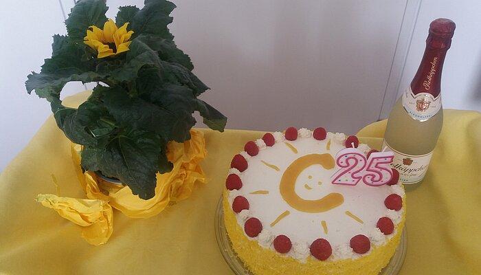 Sahnetorte mit gelbem Courage-Logo als Verzierung. Dazu eine Flasche Sekt und eine gelbe Blume