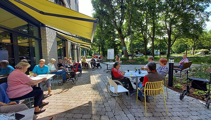 Teilnehmer der Bingo-Veranstaltung sitzen draußen bei sonnigem Wetter und spielen Bingo.