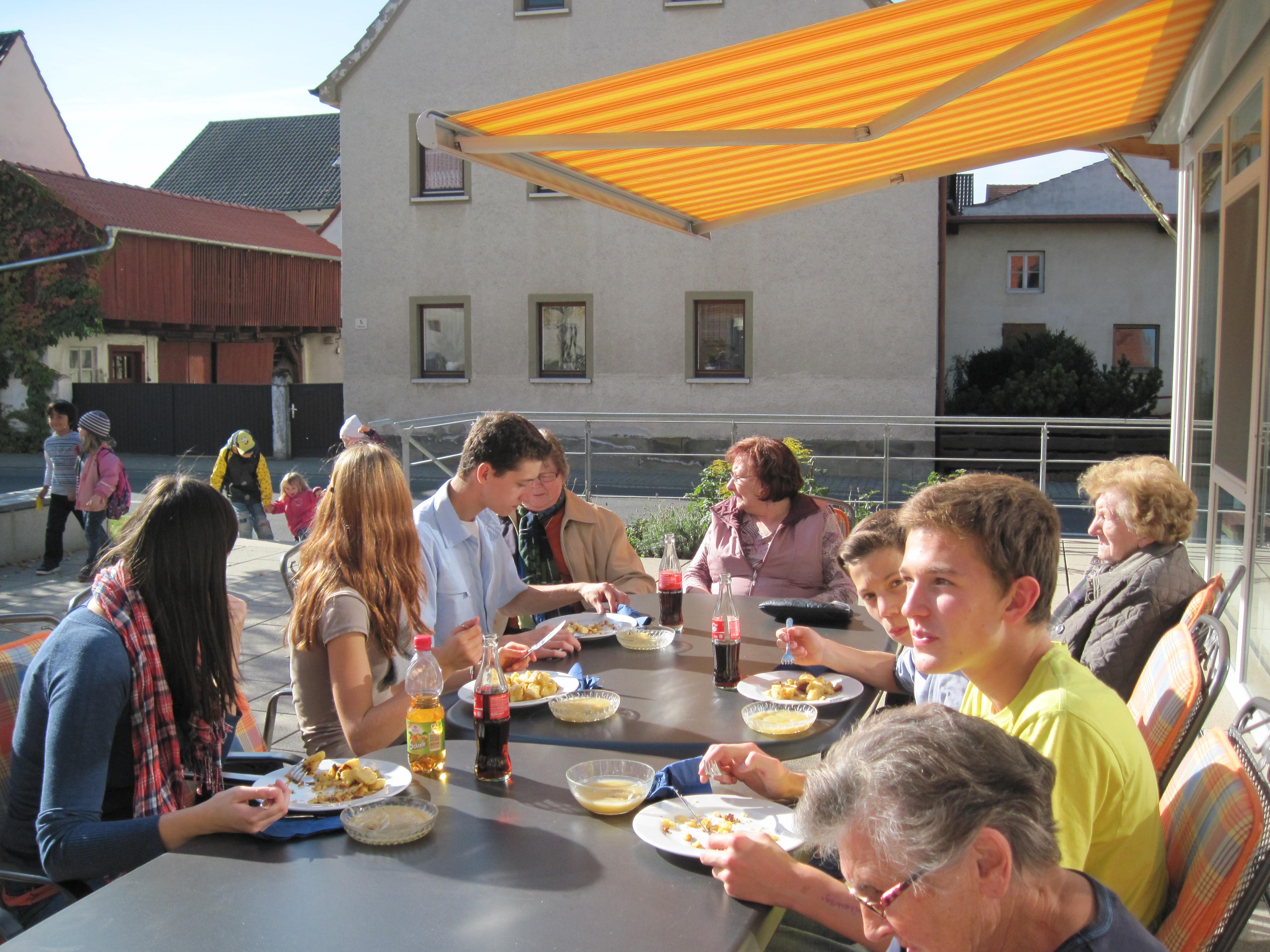 4 Erwachsene und 5 Jugendliche sitzen beim Mittagessen auf der Terrasse des MGH