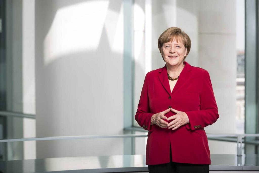 Porträtfoto von Angela Merkel, sie trägt einen roten Blazer.
