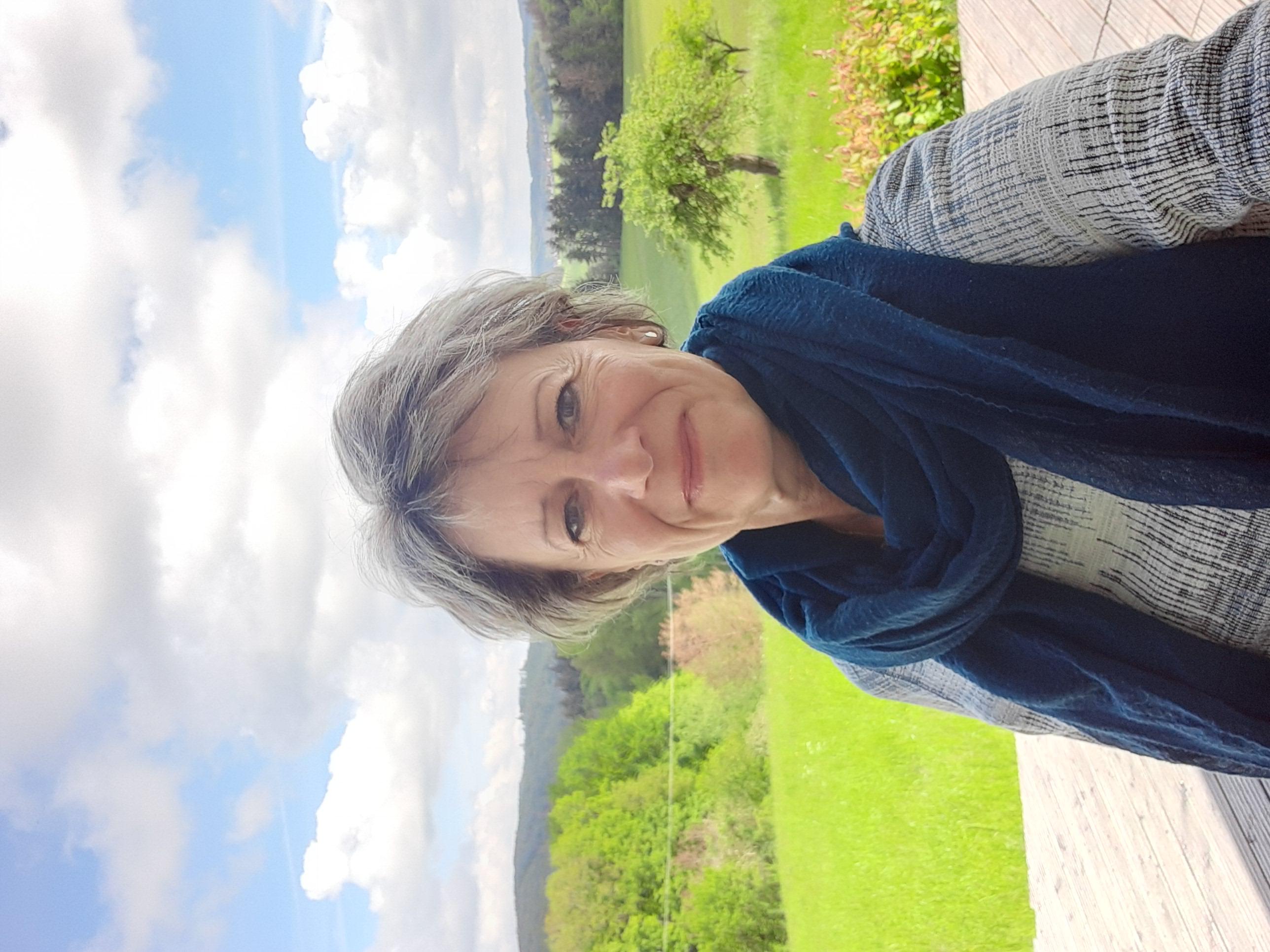 Eine Frau mit kurzen, grauen Haaren lacht in die Kamera. Hinter ihr ist ein Feld mit Bäumen zu sehen.
