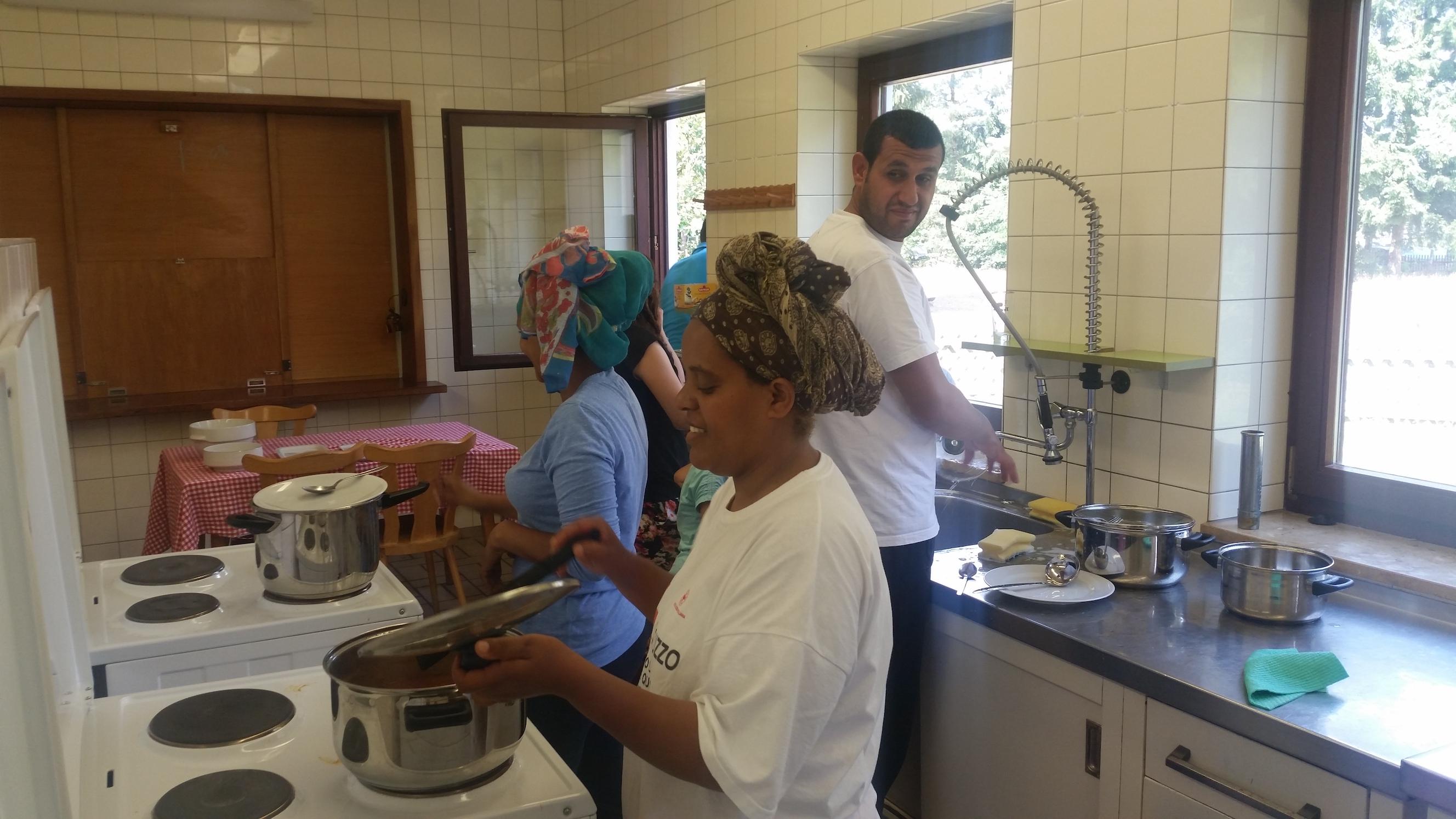 Besucherinnen und Besucher des MGH beim gemeinsamen Kochen.