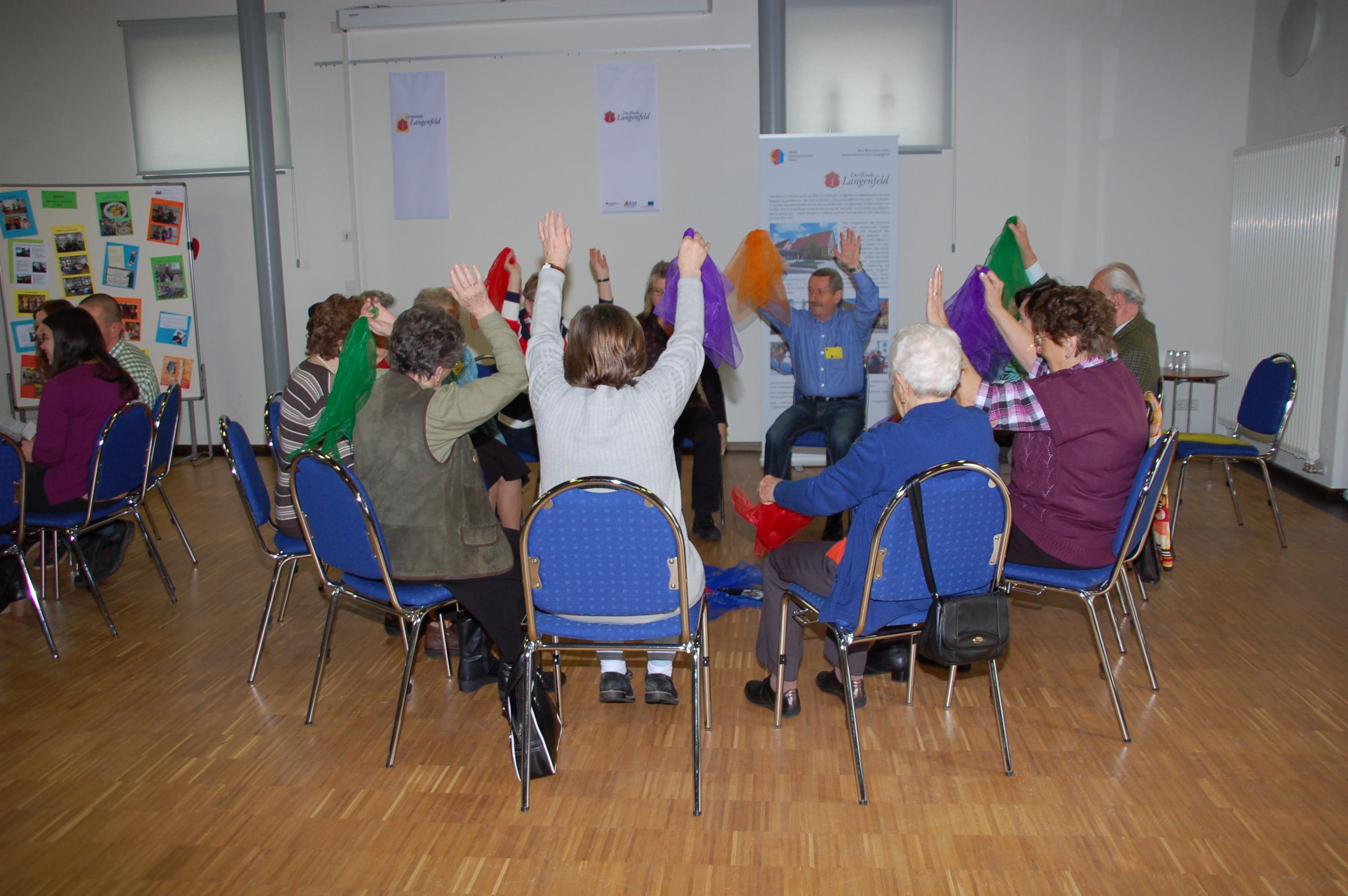 9 Senioren sitzen im Kreis zum Sitztanz