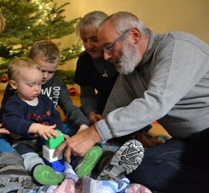 Großeltern sitzen mit zwei Jungen vorm Weihnachtsbaum und spielen