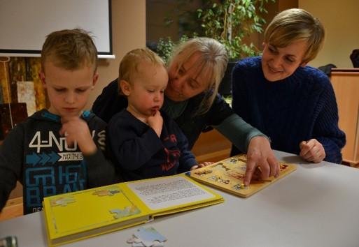 Großmutter, Mutter und zwei Jungen sitzen am Tisch und schauen Bücher an