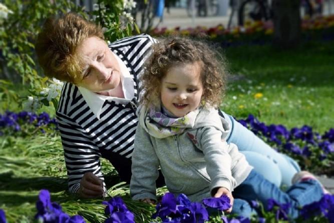 Großmutter und Enkelin sitzen auf einer Wiese und bestaunen Blumen