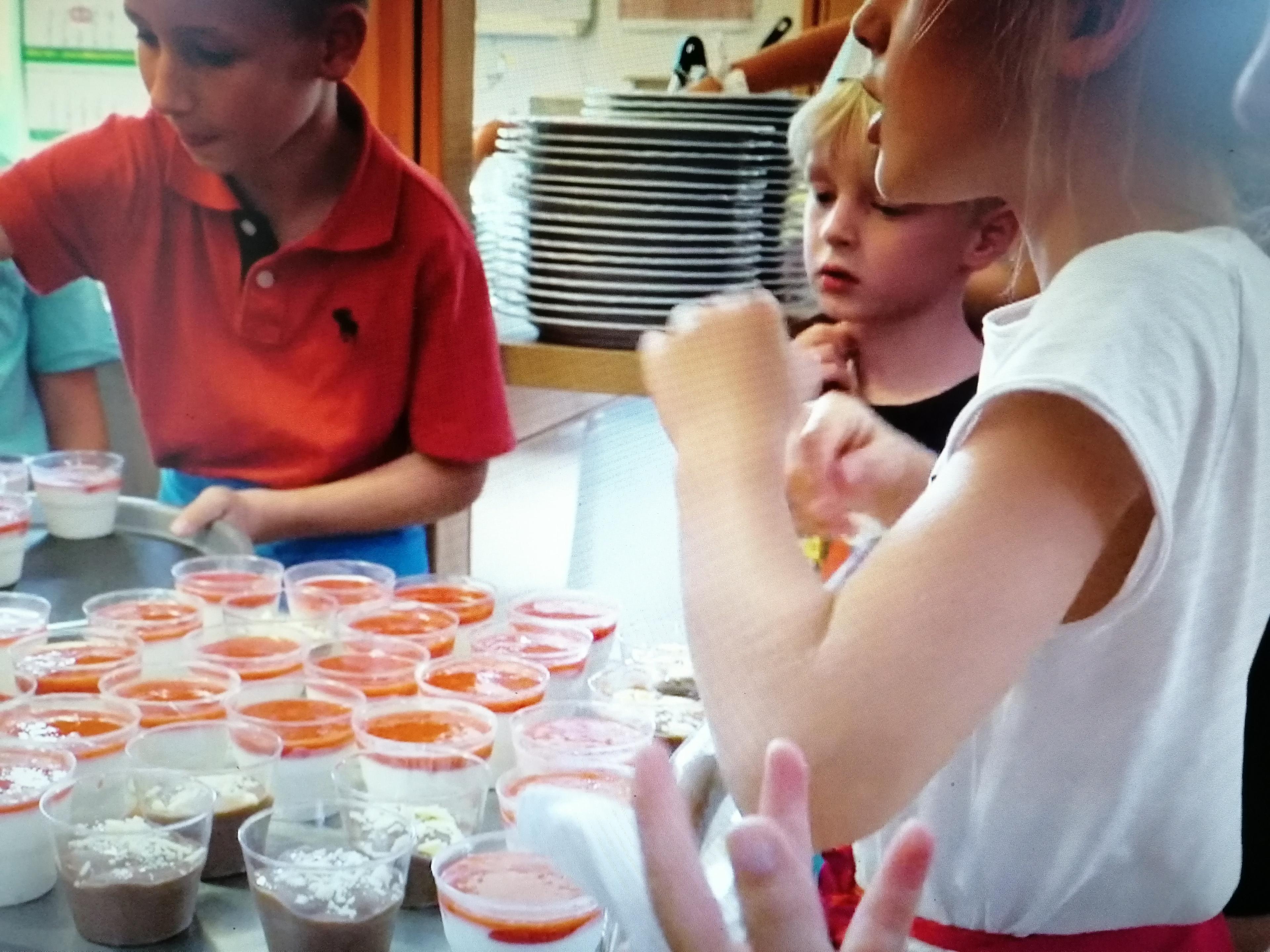 Drei Kinder füllen den Nachtisch in einzelne Portionen ab.