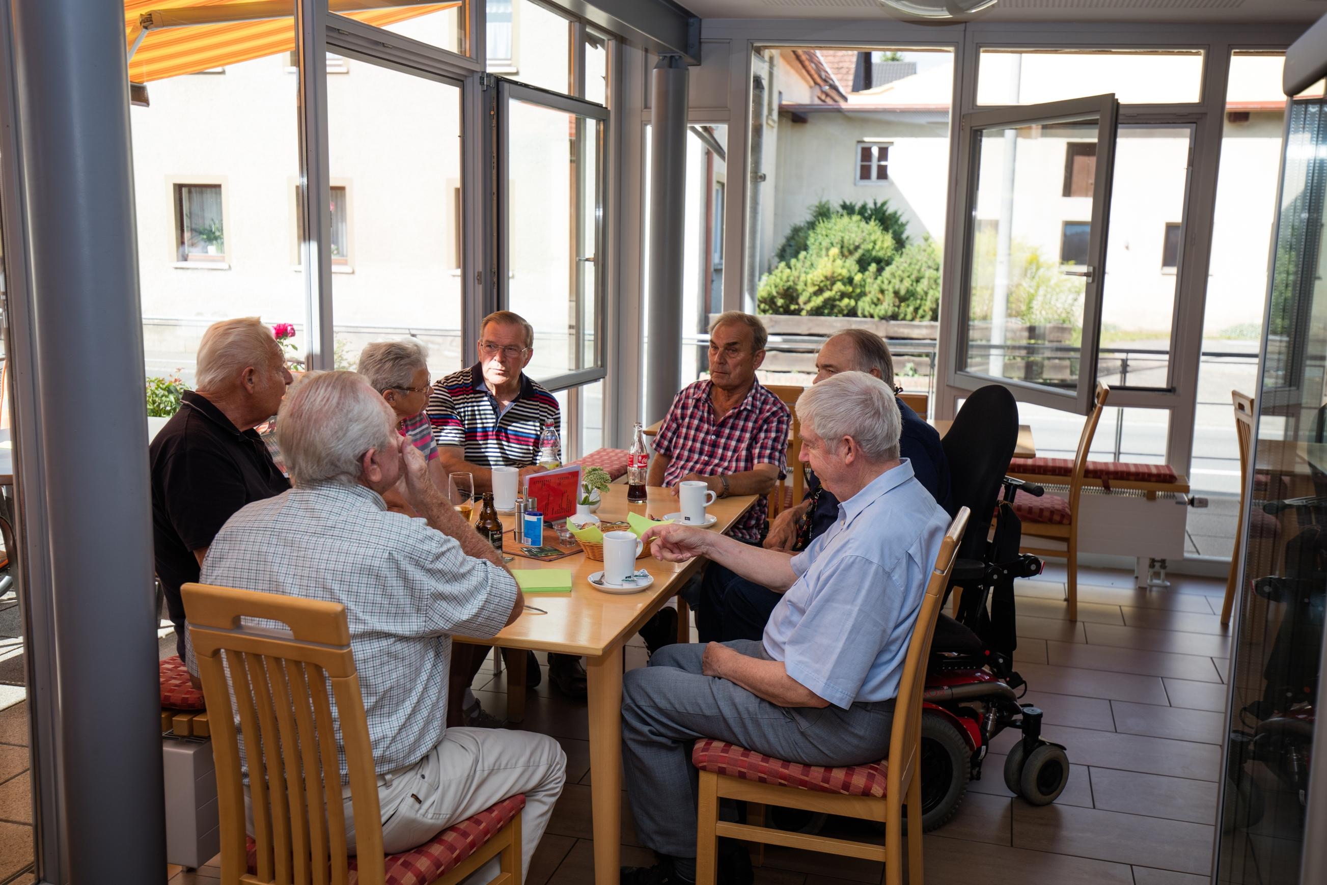 7 Männer sitzen an einem Tisch und drinken Kaffee