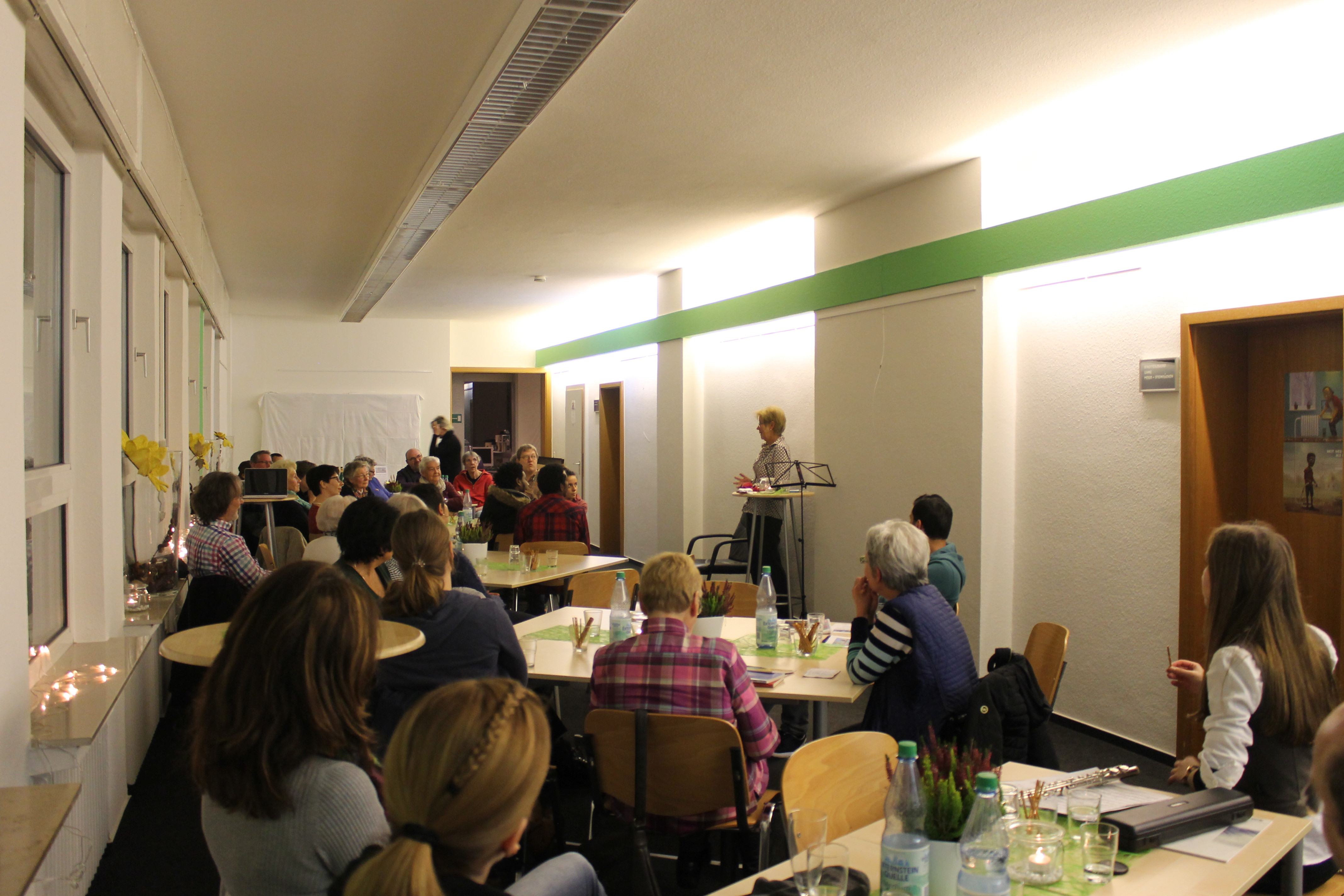 Großer Raum im MGH während der Veranstaltung, eine Teilnehmerin auf der rechten Seite