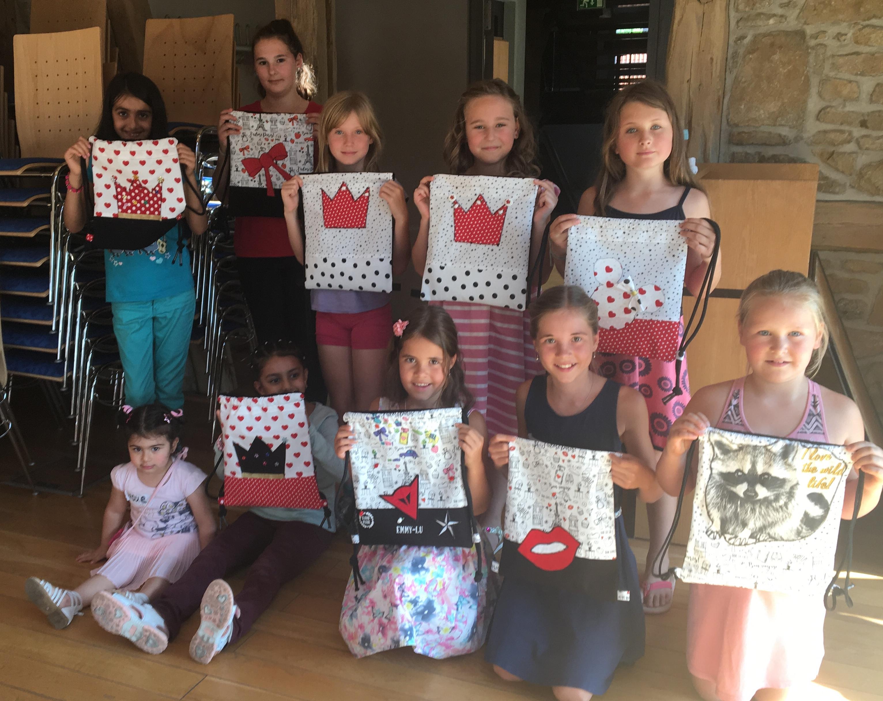 Kinder zeigen stolz Ihre selbst gestalteten Taschen.