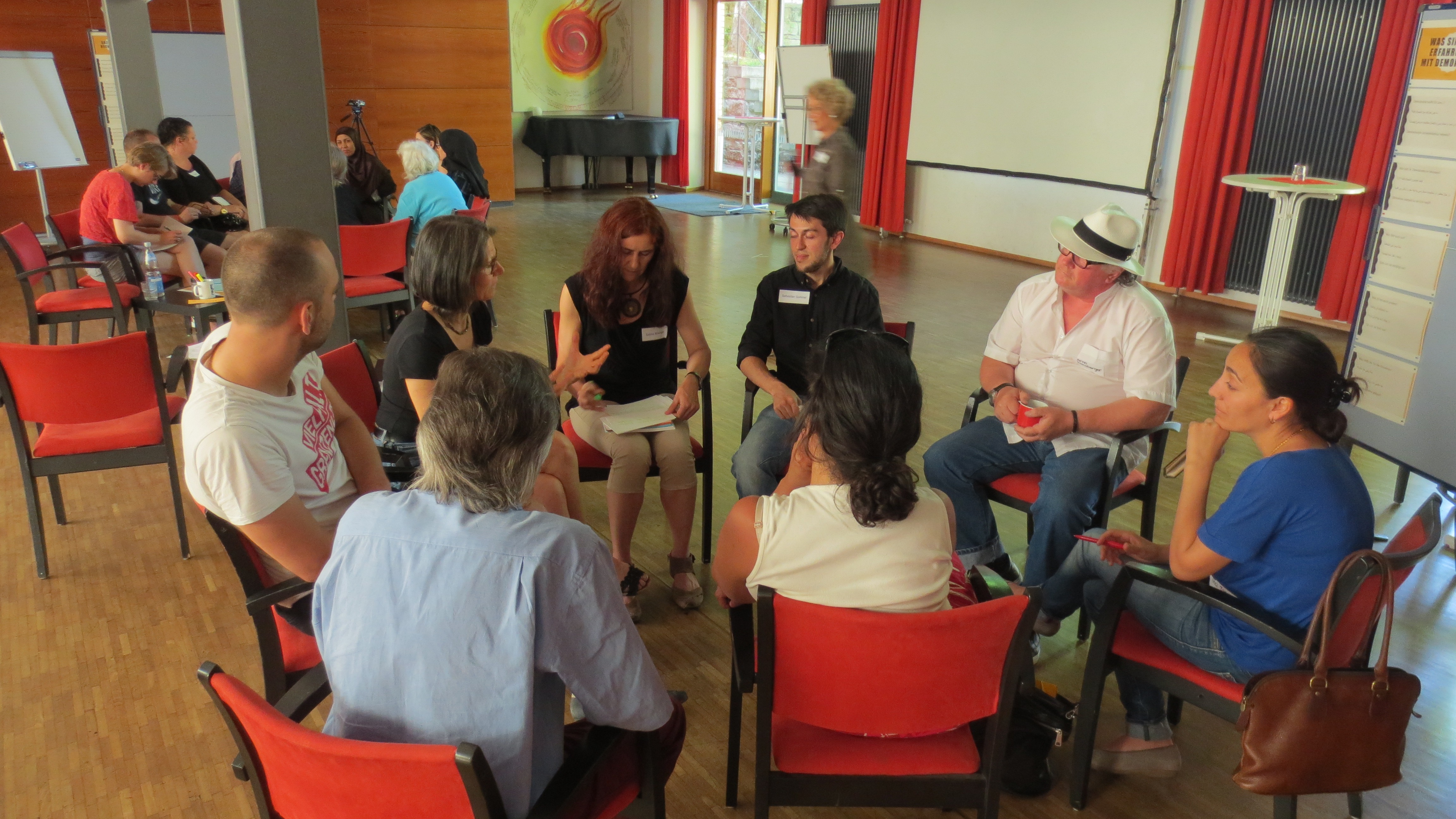 Menschen sitzen in einem Stuhlkreis und sind im Gespräch.
