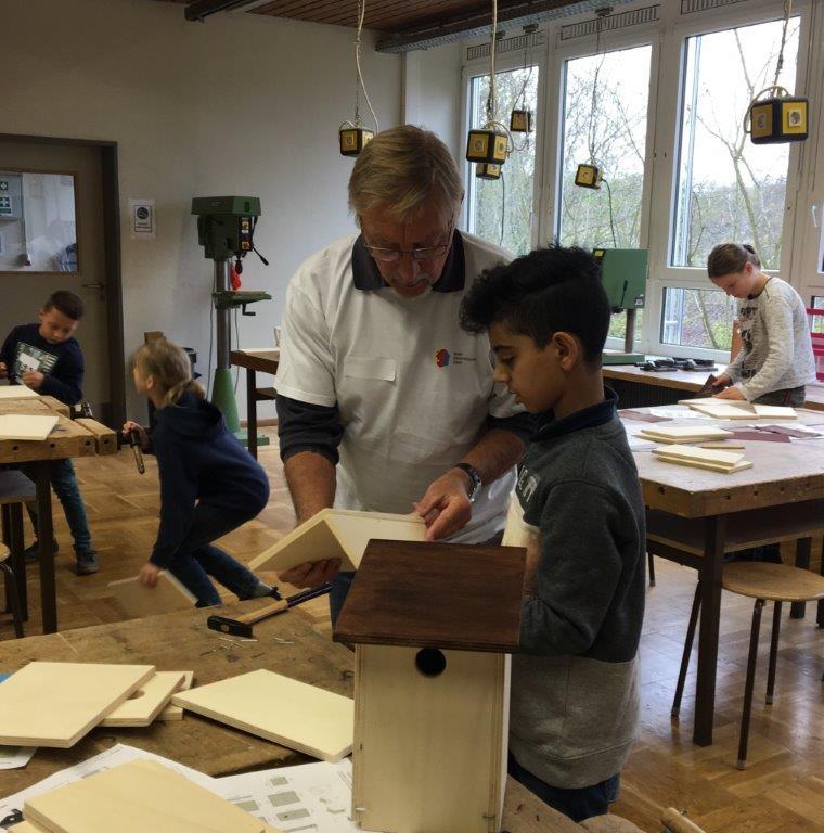 Kinder bauen unter Anleitung Nistkästen und verwenden dazu unterschiedliche Werkzeuge.