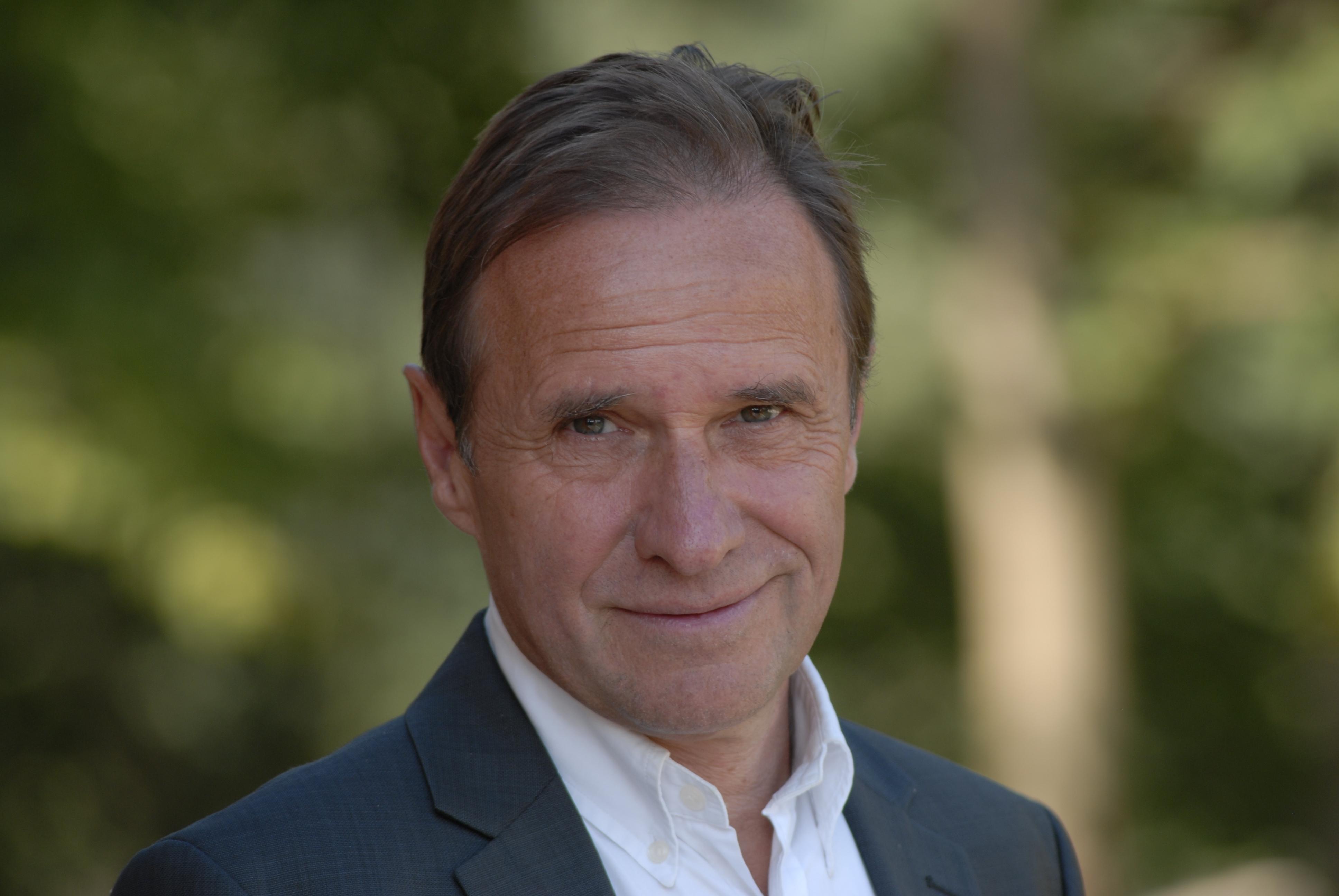 Porträtfoto von Reiner Klingholz, er trägt ein weißes Hemd, ein schwarzes Jacket und hat kurzes, braunes Haar.