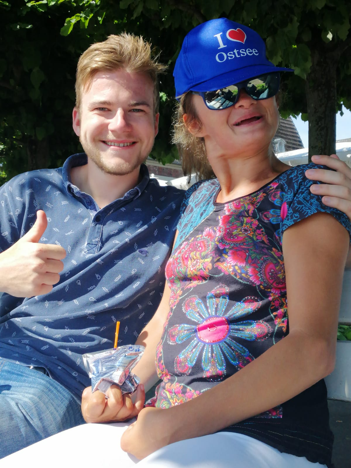 Foto von Jakob Ruch und einer Person mit blauer Kappe und Sonnenbrille.