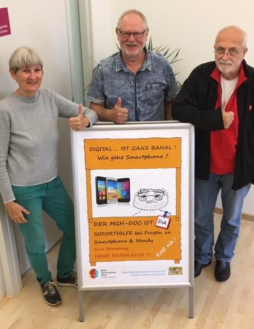 3 Ehrenamtliche aus diesem Projekt stehen mit unserem Kundenstopper im MGH