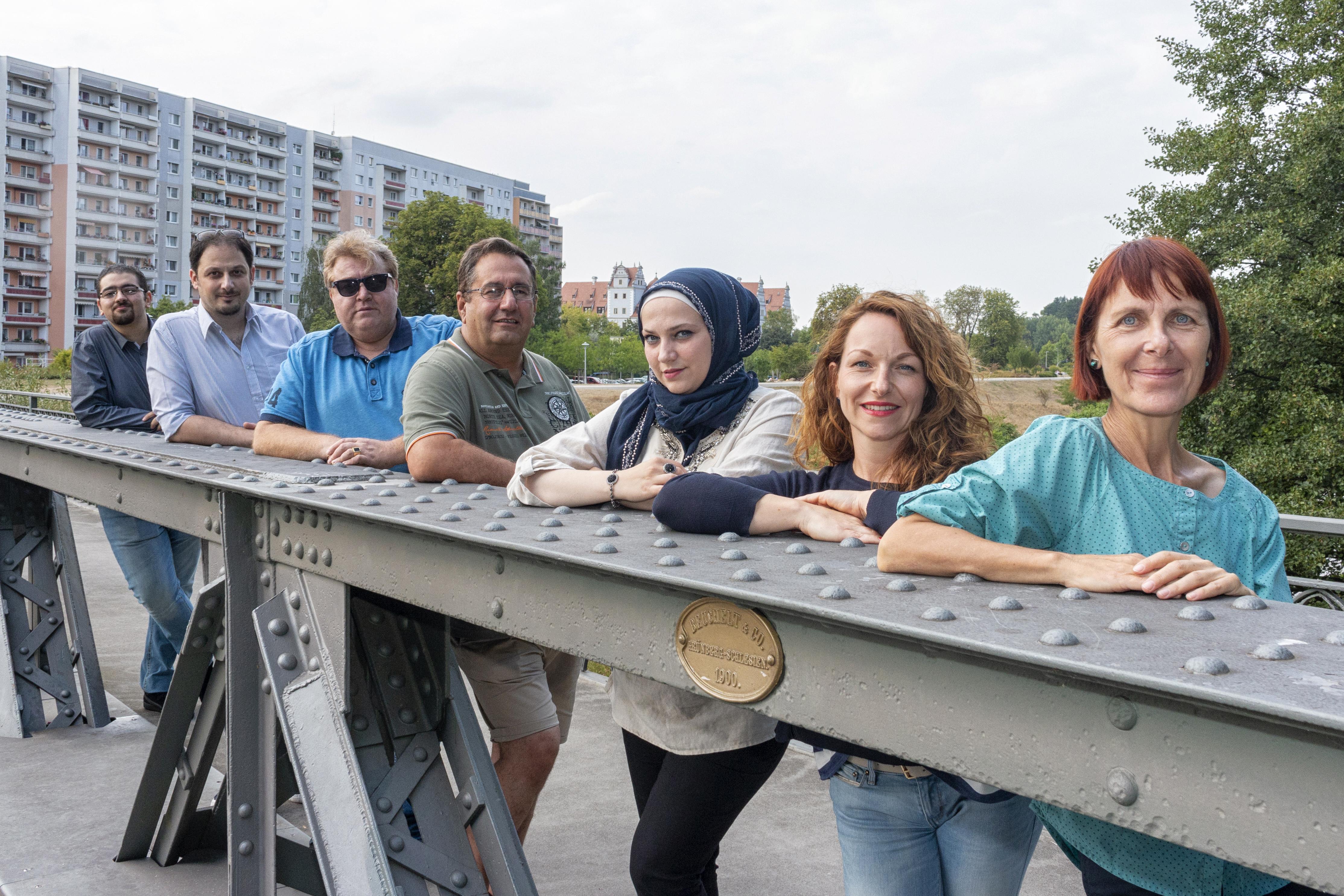 Sieben Menschen stehem auf einer Brücke. Es sind die Menschen, die zusammen die Zeitung machen.