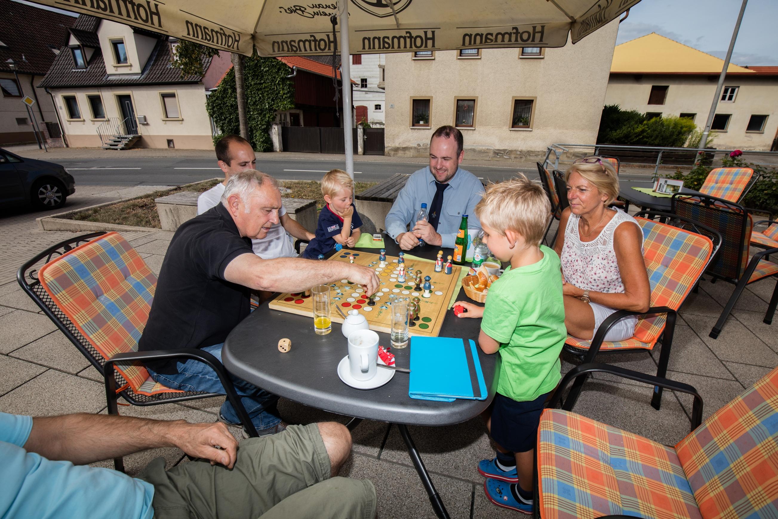 4 Erwachsene und 2 Kinder spielen ein Brettspiel auf der MGH Terrasse