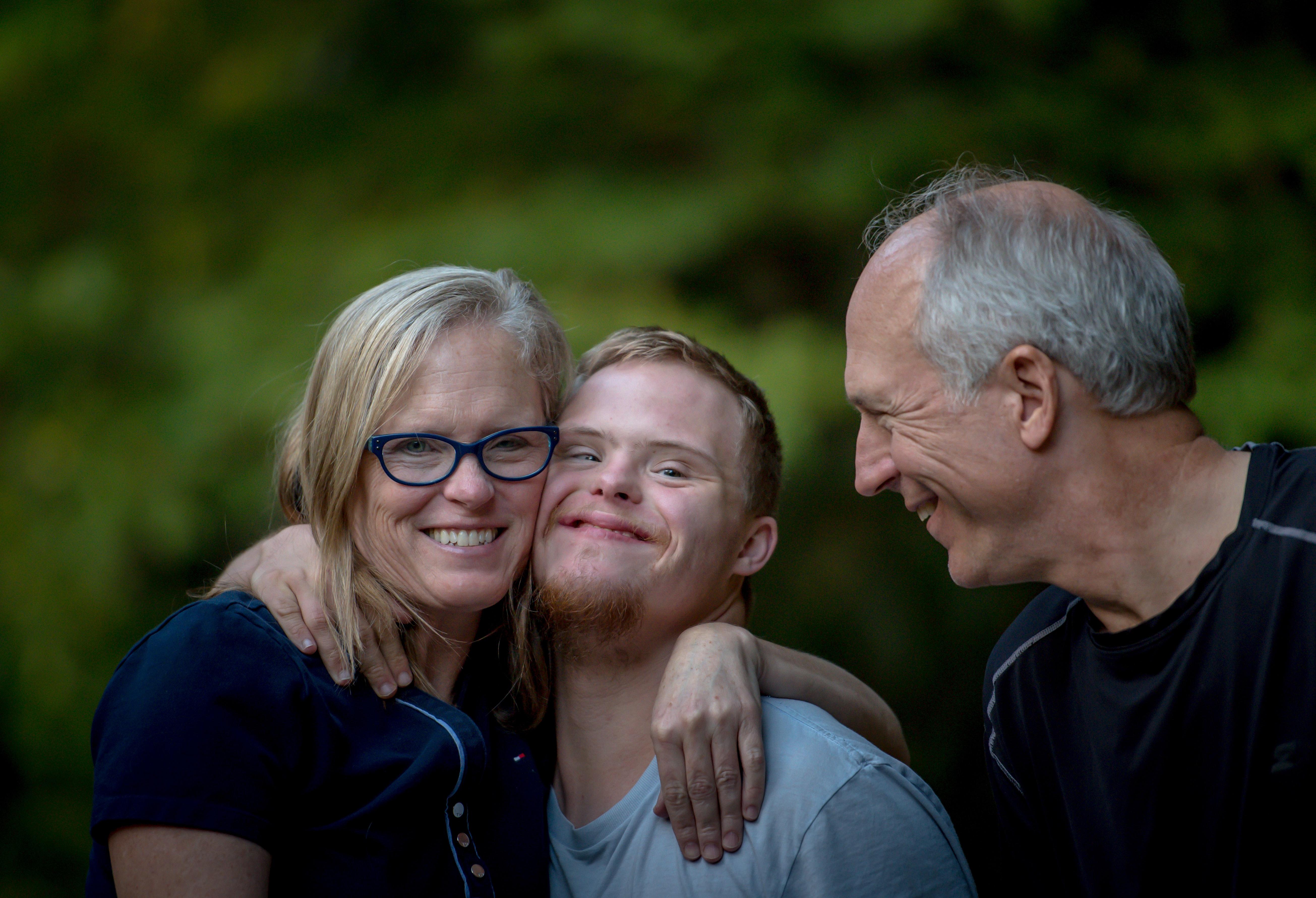 Eine Mutter und ein Vater mit ihrem Sohn in ihrer Mitte, alle drei lächeln.