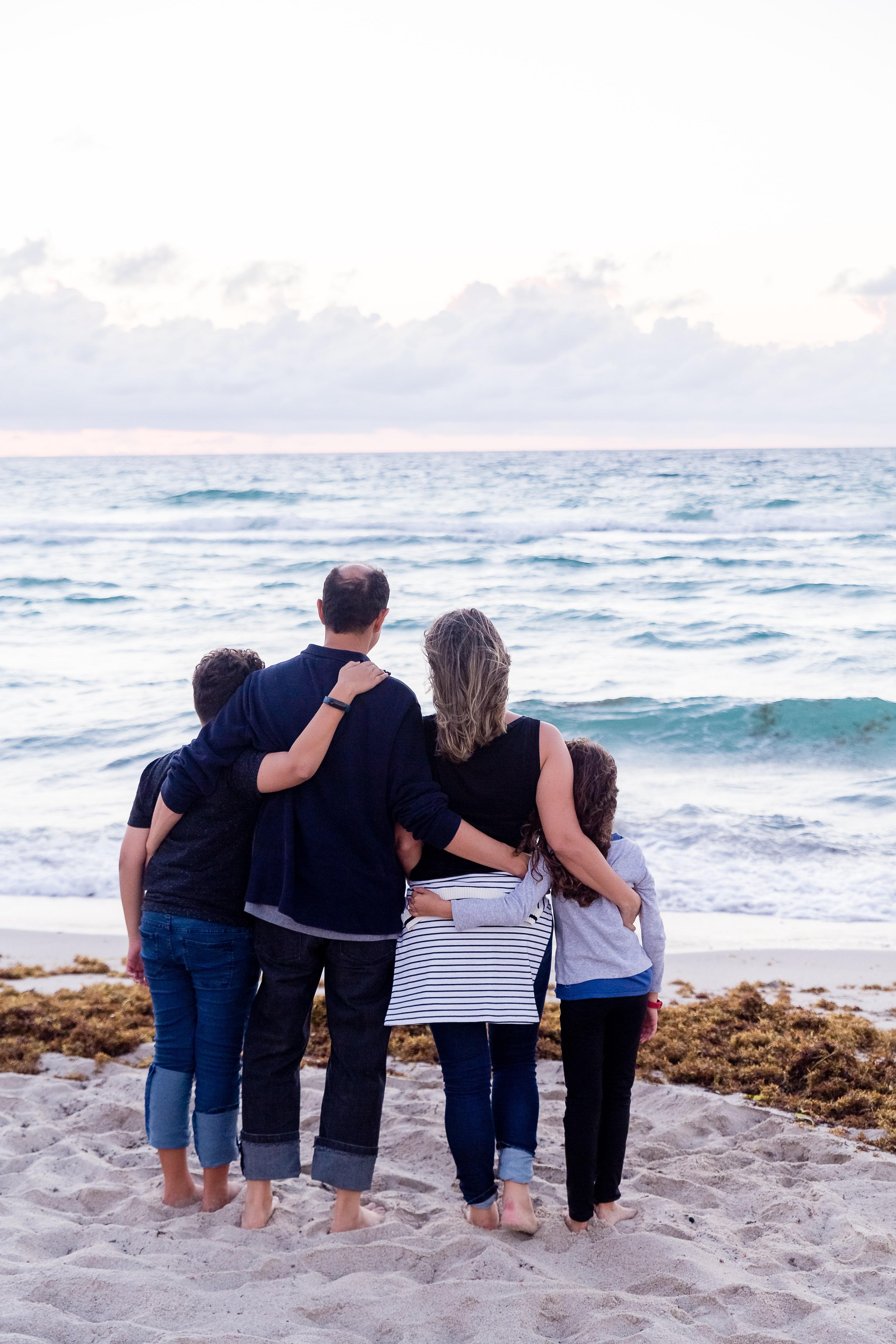 Vierköpfige Familie, welche man von hinten sehen kann, wie sie sich in den Armen halten