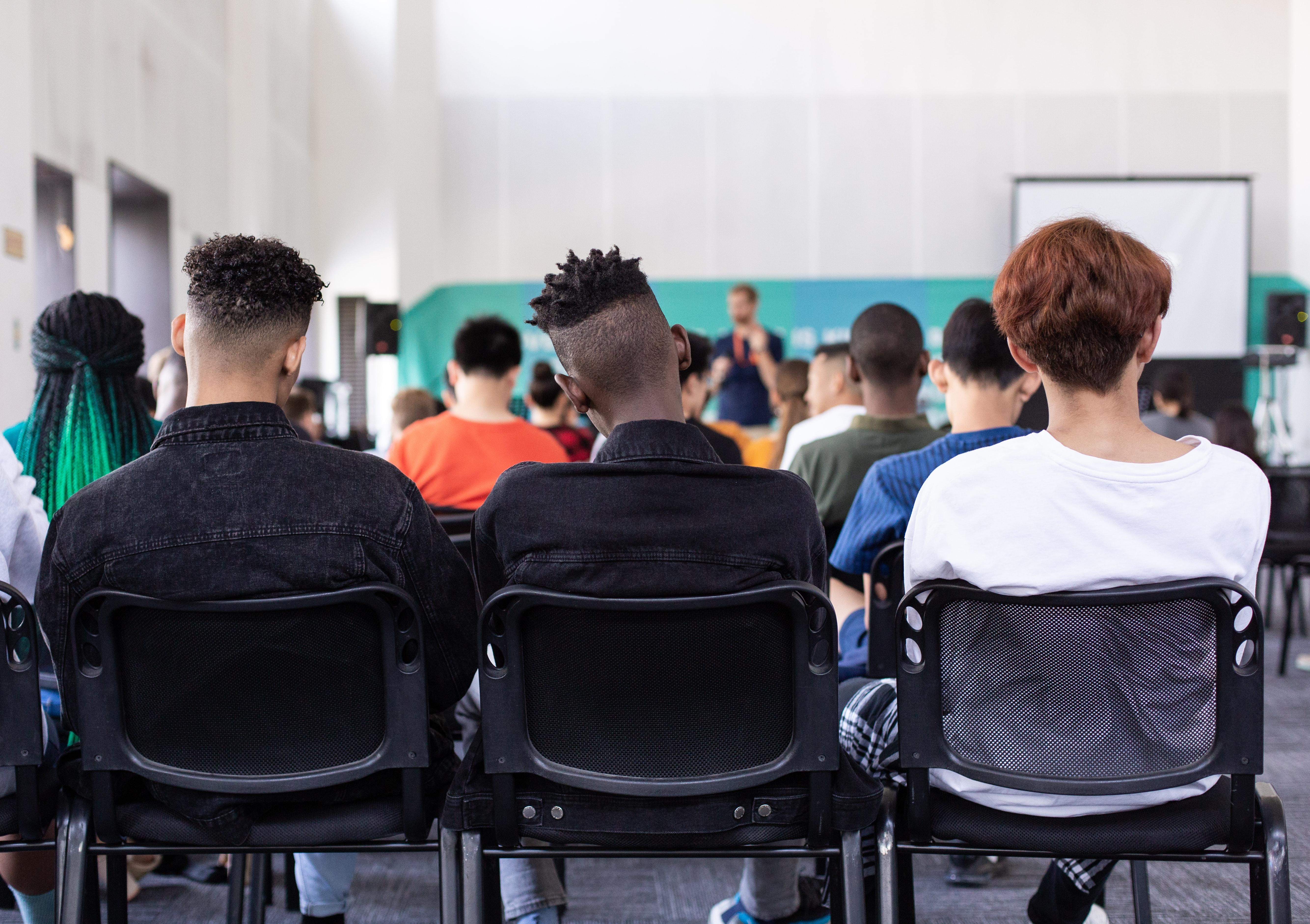 Klassensituation, drei Jugendliche sind von hinten zu sehen.