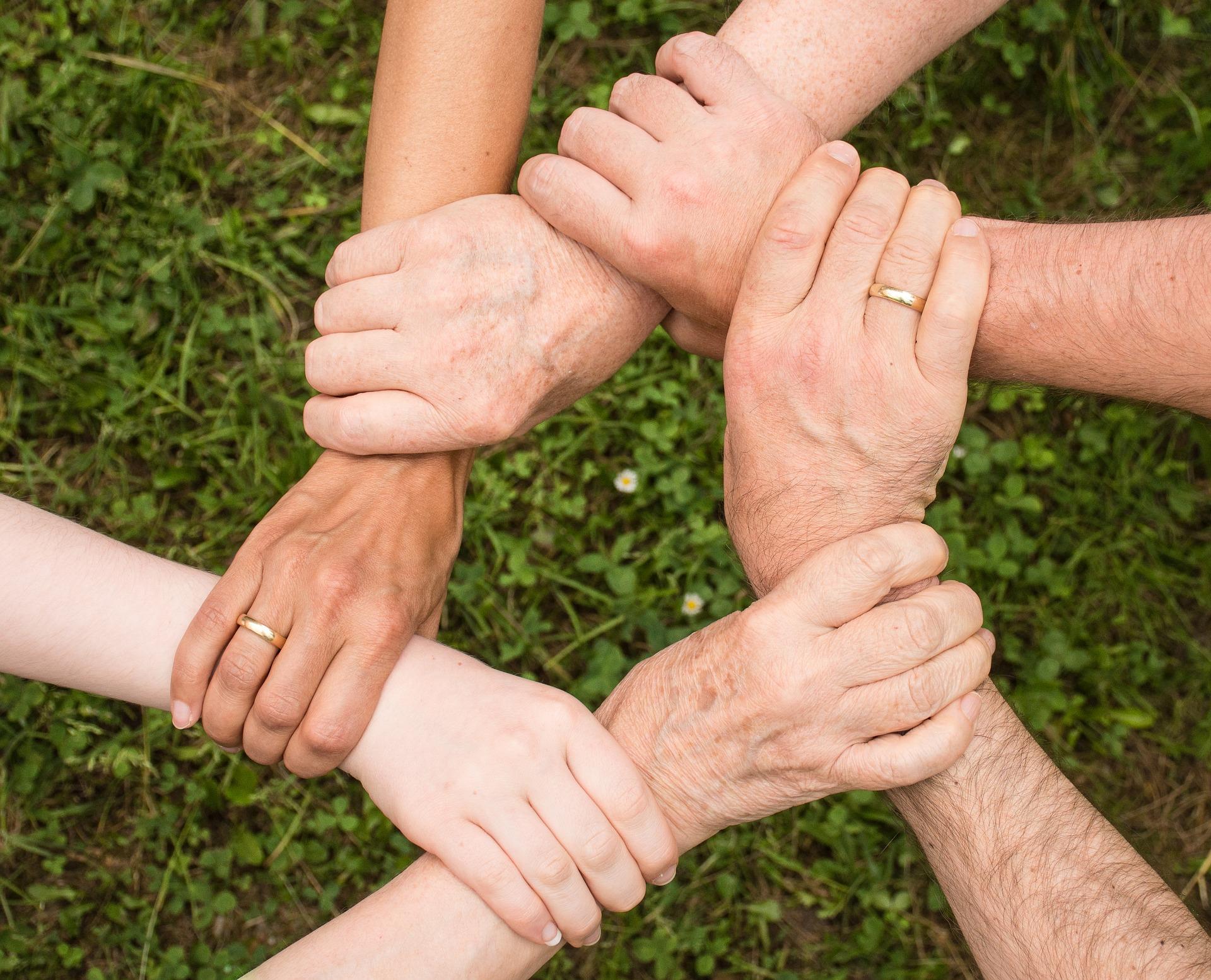 Hände, die sich umschließen und so ein Netz formen.