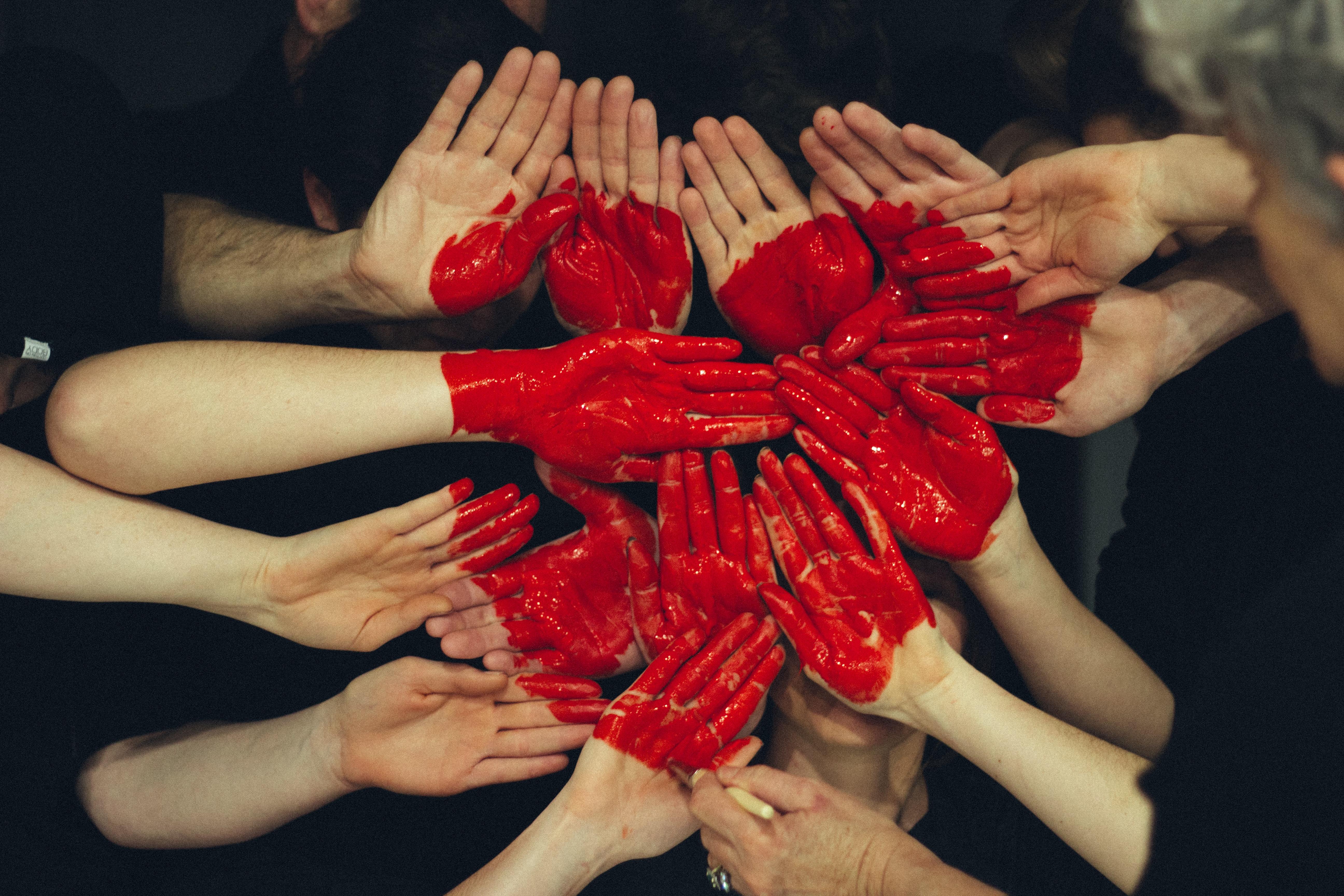 Zahlreiche Arme von Menschen sind ineinander verwoben, in Rot ist ein Herz über alle Arme gemalt.