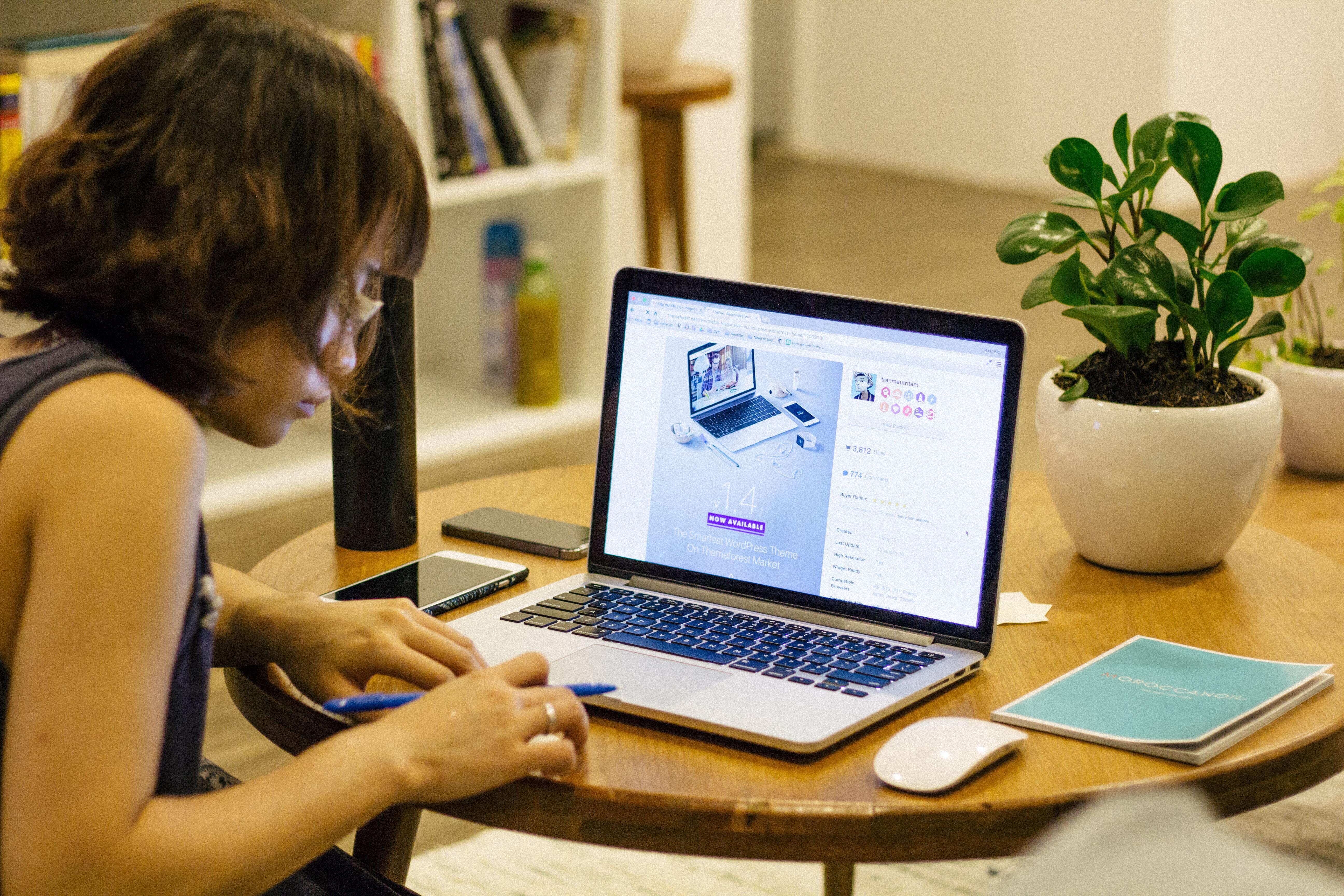 Frau sitzt an einem runden Holztisch und arbeitet an einem Laptop.