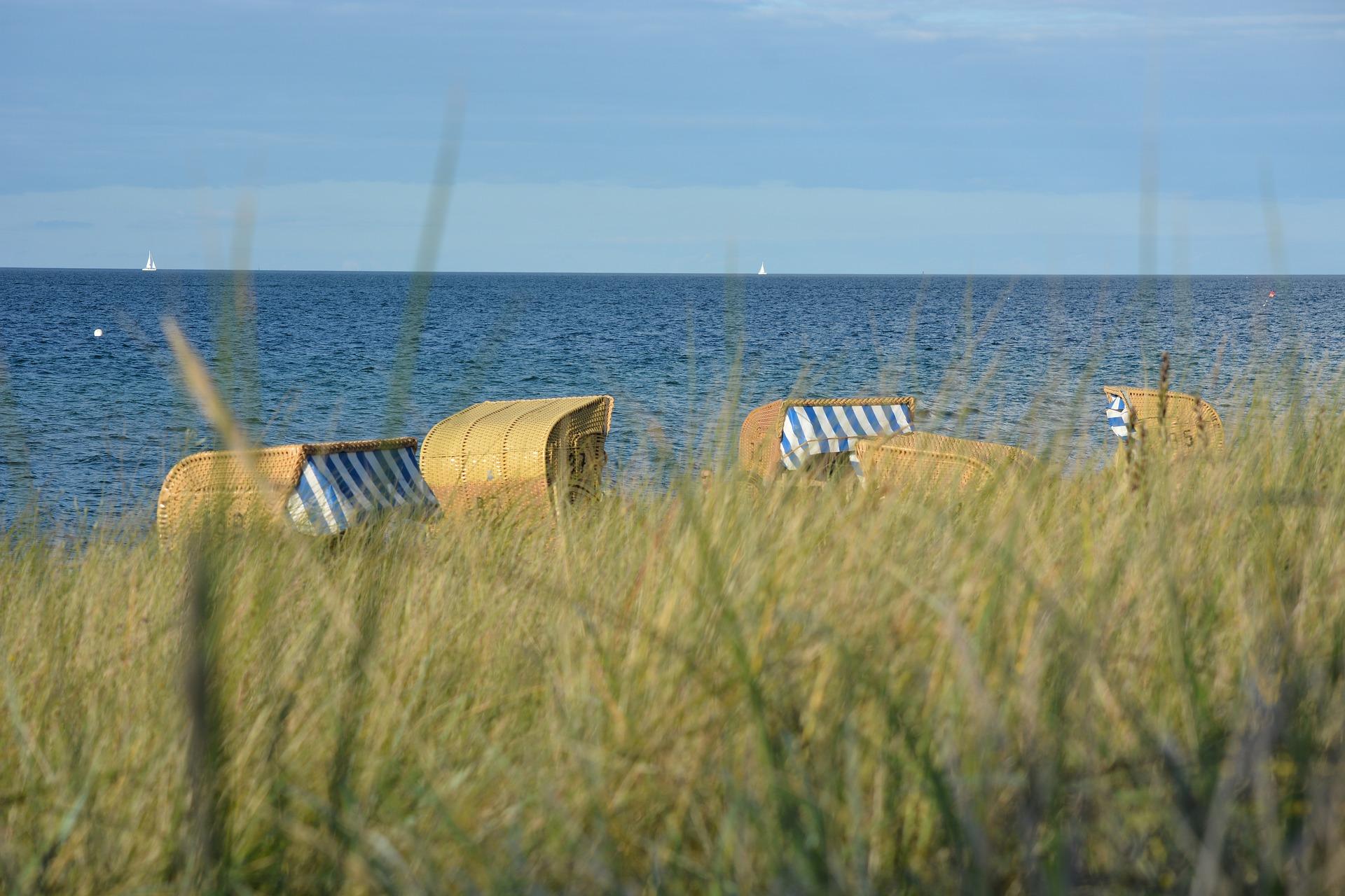 Dünen im Vordergrund, im Hintergrund einige Strandkörbe und das blaue Meer.